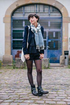 blue and white scarf, navy blue blazer, navy blue shirt, dark wash denim shorts, black tights, canvas bag, black moto booties
