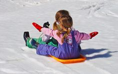 Day 15: Keep the kids active this winter!   Girls sledging on a snowy hill.   #healthy #advent #christmas