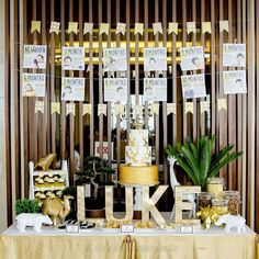 Cake and dessert buffet setup for a golden geometric safari first birthday party. A unique gold and white baby party theme for a little boy!