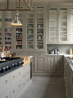 Glass fronted kitchen cupboards, allow you the open shelf feel, with out everything getting greasy/dirty!
