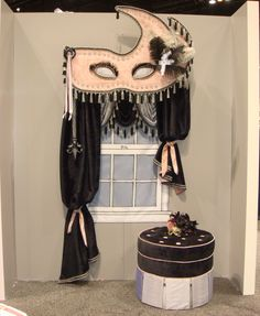 Robin Jordan of LaRuche Window Couture created this wild window treatment showcasing her fabrication skills. Picture this at a (masquerade party or ball) or other larger than life event.  Note the curved cornice outlined with cords and diamondhead trim and accented with tassels and feathers.