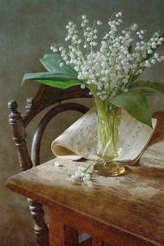 Lily Of The Valley - nikolay-panov. still life with bouquet of lily of the valley in yellow glass vase and vintage music book on wooden table, old chair near table is illuminated by daylight Still Life Photos, Still Life Art, Deco Floral, Arte Floral, Woodlands Cottage, French Country House, Country Living, Still Life Photography, Ikebana
