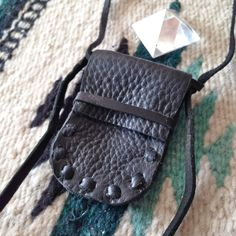 """? Handcrafted black deer tanned cowhide medicine pouch. Simplicity to hold your treasures. Fold over flap. Whip stitch construction. ? Each piece is made to order and will vary slightly. Please allow 7-14 days for completion.? Measurements:width: 2""""height: 3""""total strap length: 29""""? This piece can be made with various colors of leather. Please send us a message if you are interested in a custom piece."""