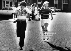 Elton John runs with a friend through a Dutch street in 1975