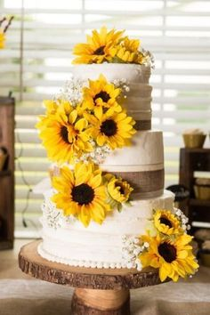 Scrumptious sunflower and baby's breath adorned wedding cake on rustic wood round