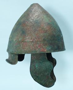 Greek bronze Pilos helmet, of conical form with a recessed carinated band around the lower portion. Ca. 400-300 BC. h. 35 cm. Pilos helmet takes its name from felt shepherd's cap whose form it replicates. This helmet came into use during later Peloponnesian War, replacing earlier more closed and restrictive forms like Corinthian. Pilos was especially favored among Macedonian cavalrymen of 4th c BC. Helmet appears prominently on Macedonian coinage of Alexander the Great and his successors.