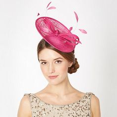 938cfa8cc7c This small pink saucer fascinator has a mesh upper with a central looped  bow and headband fastening. It comes with a feather trim and pink  rhinestone detai…