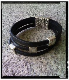 Brazalete en Zamak, triple cuero plano negro, con decoración cuadrados ruan sin fin y cierre labrado imán.