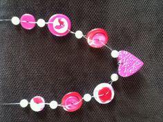Halsketting gemaakt door twee verschillende maten cirkels uit Fimo te stansen. Maak een gaat in het midden. Neem twee draden, rijg deze kruislings door de Fimo-schijfjes!