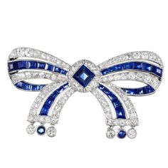 Platinum 1920s bow pin, signed Cartier and set with an EGL-certified no heat sapphire in the center, then further decorated by additional sapphires and 2.50 diamonds. 1.75 by 1 inch.