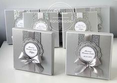 Zaproszenia na Pierwszą Komunię Świętą w pudełku w srebrnym kolorze z dodatkiem brokatu oraz szeroką, srebrną wstążką