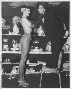 """Performers preparing backstage for the Folies Bergere show at the Tropicana Hotel, Las Vegas, August 1986. The tallest showgirl in Las Vegas, Sonja Lubbers (6 feet, 2.5 inches), is adjusting the tie of the show's shortest boy dancer, Bo Ramos, who is standing on a chair.  Image is part of UNLV Libraries """"Photo"""" digital collection."""