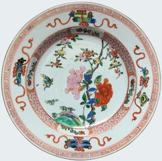A Chinese famille rose-verte plate painted with flowers and auspicious objects. Yongzheng period. China/Asia. Richly enameled in the famille rose-verte palette, with a butterfly foraging pink and red peonies, green rocks ; the rim decorated with ribbon-tied auspicious objects.