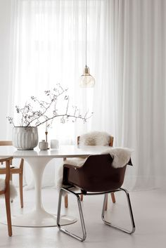 Scandinavian design idea. Beautiful dining room with white round table, clear pendant light and from floor to ceiling white curtains