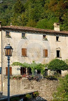 Photo made in Cison di Valmarino, the exhibition dell'artigianto, in the province of Treviso in the Veneto (Italy). In the photo, taken by one of the many streets full of stalls, we see a typical house of the country, close to the mountain, with a low wall in the rock on which are flowers. In front of the house and on the left a street lamp.