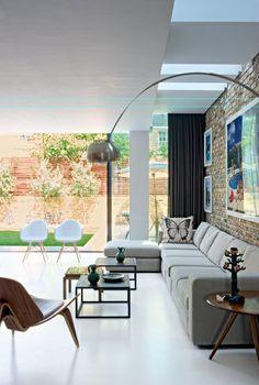 Salon contemporain avec des pièces iconiques comme le lampadaire Arco de Castiglioni, le fauteuil de Hans Wegner ou les Eames Plastic DAW