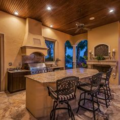 For the grill area and island, granite countertops enhance the elegance of this coastal outdoor kitchen by Florida's Ryan Hughes Design.