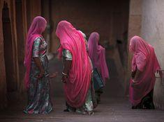 Imagem de mulheres indianas em véus que andam abaixo de uma escada