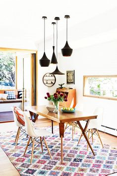 Bright dining space with a cluster of black pendant lights, a printed area rug, and modern chairs
