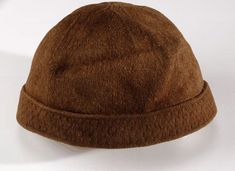 This light brown woollen knitted cap was discovered on a man's body found at Gunnister in Northmavine in Shetland, in the late 17th century. When he died, the man was wearing a coat, jacket, shirt, breeches, cap and stockings.  The cap has been knitted mainly in a stocking stitch pattern - one row plain and one row purl. The turned up brim has a more elaborate pattern.