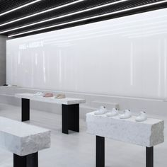 Axel Arigato London store Christian Halleröd Shoes are displayed upon plinths made from giant pieces of terrazzo inside this minimal boutique in Soho by architect Christian Halleröd. It features a simple palette of concrete, metal and mirrored surfaces to complement a white colour scheme.