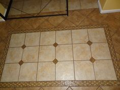 Love. Tile design at entry.  Has both colors of tile that are througout the house, plus diamonds of granite from the kitchen counters plus a roman style mosaic for the edging