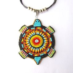 This large medallion necklace was made by Ruby Decoteau (Turtle Mountain Chippewa) and features seed beads in blue lake and fire colors on hide. >> shop.beyondbuckskin.com #native #beadwork #turtleisland #chippewa