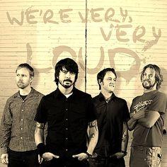 Los Foo Fighters dándonos una lección de estilo y comodidad! Además para enseñar tatuajes, qué tal una buena camisa sport negra, manga corta, con camiseta blanca abajo, mulequera y pulsera de liga.
