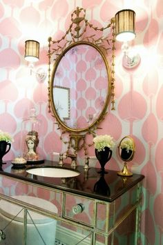 """A mirrored chest of drawers has been transformed into a vanity with sink in this home's powder room...the gilt mirror, shaded sconces and the pink 'fan' wallpaper all create a feeling of decadent luxe."""
