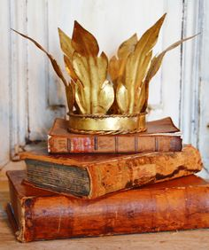Design Studio Rare Antique French Laurel Leaf Gilt Crown- The tattered books do it proud. Really the books are past highly collectable (unless rare) when in this shape but how nice as décor? Love it.