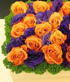 This is a cube vase floral arrangement that features roses and lisianthus in an orange and purple color scheme.  See our entire selection at www.starflor.com.  To purchase any of our floral selections, as gifts or décor, please call us at 800.520.8999 or visit our e-commerce portal at www.Starbrightnyc.com. This composition of flowers is generally available for same day delivery in New York City (NYC). SQ086
