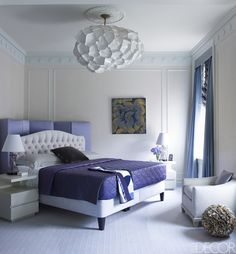The custom-made bed in the master bedroom is upholstered in a Pierre Frey fabric, the screen is covered in a fabric by Sahco, and the bedside tables are by Crate & Barrel; the light fixture by Christopher Trujillo is constructed of paper plates, the curtains are of a fabric by Pollack, and the carpet is by Beauvais Carpets.   - ELLEDecor.com
