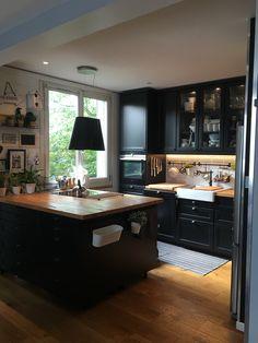 J'adore cette cuisine Ikéa noire avec ce plan de travail en bois brut et son îlot central