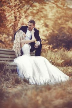 Bride sitting at a bench with groom sitting on top of it