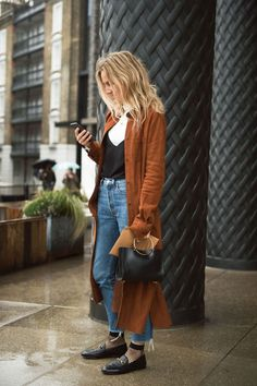 long amber colored coat with black loafers