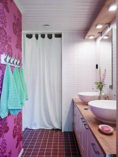 Kylpyhuoneen altaat, hanat, kaapisto, peilit ja valaisimet on ostettu valmiina kokonaisuutena Habitaresta. Seinät on rakennettu vasta sen jälkeen kalusteen mittojen mukaan. Valkoisen verhon takana on pieni kodinhoitotila. Kaikki kaakelit ovat Laattapisteestä. Pinkki tapetti on Designers Guildin. Vasemmalla kulman takana on wc-istuin.