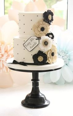 white and black wedding cake with gold flower