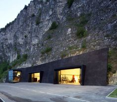 Fire Magreid, Italy/ A rock face is the location of the new volunteer fire brigade of margreid on the wine street. Three big caverns are drilled into the rock and interlinked with a cross cut. A black pigmented concrete wall stands in front of the rock, with the same inclination as the mountain. The three caverns dock on to this concrete wall.