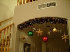 Lighted garland over entryway with hanging ornaments