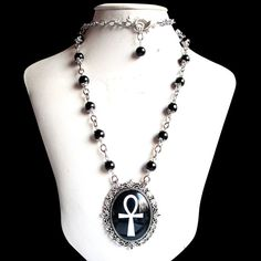 "Ankh Necklace Gothic Egyptian Stylish black and white Ankh pendant, glass cabochon. Comes with a sturdy chain adorned with black glass beads. The lengths of the chain is about 70 cm and it is adjustable. Has a great quality lobster claw clasp. Size of the pendant is 48 x 60 mm.   The Ankh is also known as key of life, the key of the Nile or crux ansata (Latin meaning ""cross with a handle""), was the ancient Egyptian hieroglyphic character that read ""eternal life""."