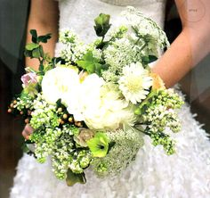 The bridal bouquet will be a loose clutch of blush pink peonies, juliet garden roses, pink hellebores, white stock flower, white scabiosa, peach hypericum, pink and green parrot tulips, geranium foliage, blush pink waxflowers, and blush pink spray roses wrapped in balck satin ribbon in a bow.  The bridesmaids will have bouquets similar in texture and shape with flowers in shade of ivory and white.