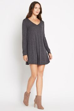 Ribbed, heathered grey material crafts this swing dress for a lovely cold weather outing. Shaped by a v neck, long sleeves, and a round hemline for total-body fullness. Pair with your favorite ankles booties! This dress is unlined.