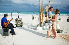 Unique ceremony set-up on the beach of Tulum with bamboo, bird cages, flowers and a lone guitar. Mexico wedding photographers Del Sol Photography.