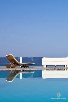 Sunloungers by the swimming pool at the Rocabella Santorini