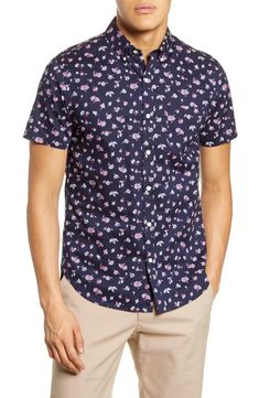 Ditsy flowers scatter in pinks and whites against the deep, dark blue of a sport shirt cut from cotton poplin with short sleeves and a button-down collar.