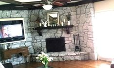 """1970s Stone Fireplace Makeover -- How to use paint but keep it looking natural. Clean the stone with a little soapy water. Vacuum all the little pebbles and sand from the grout and stone surface.Drop cloth on floor and tape the edges.Tape.Paint the entire face, including grout, with watered-down """"Annie Sloan Chalk Paint"""" in """"Paris Grey"""". Add some white (flat) latex house paint to the ASCP mixture then dry-brush:lightly accent the stone peaks, not the valleys."""