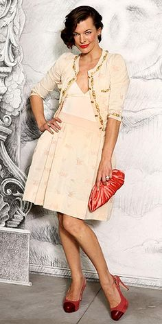 MILLA JOVOVICH  Also at the Chanel show in Paris, the star goes for retro glam in an A-line cream skirt, gold-trimmed cardigan and coordinating red accessories including cap-toe heels and a clutch.