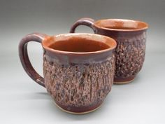 Pair of textured, brown and shimmering pink wheel thrown pottery mugs.
