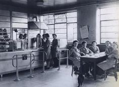 Fulwell trolleybus depot. Interior view of the depot canteen showing a group of female uniformed staff seated at a table. Two female members of canteen staff stand behind the servery area.    Photographed by Topical Press, 1947