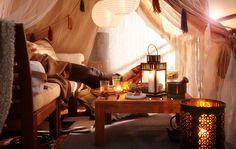 Tent in bedoeïenenstijl op een balkon. Er ligt iemand op de zachte bank thee te drinken en er staan kaarsen op de grond en de tafel voor de gezelligheid.